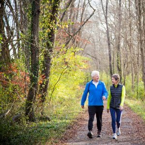 Couple walking down forest trail